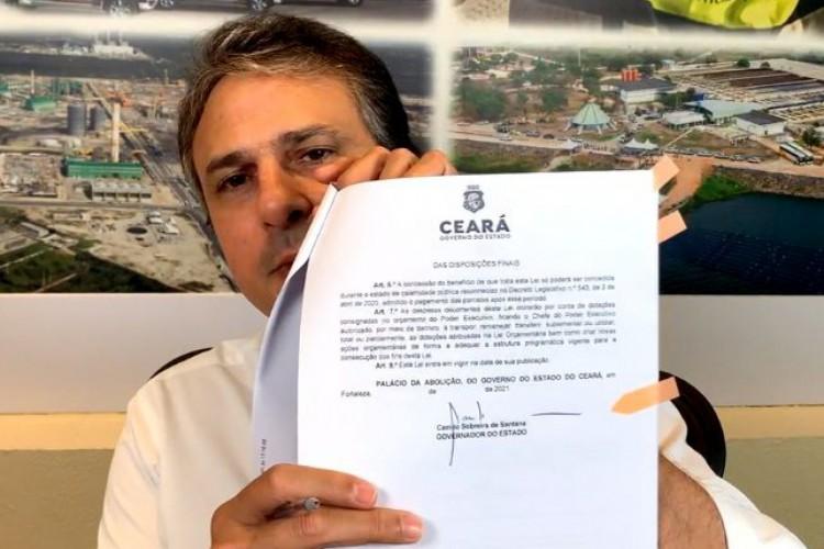 Camilo mostra assinatura da sanção do programa Mais Emprego Ceará (Foto: Reprodução Facebook)