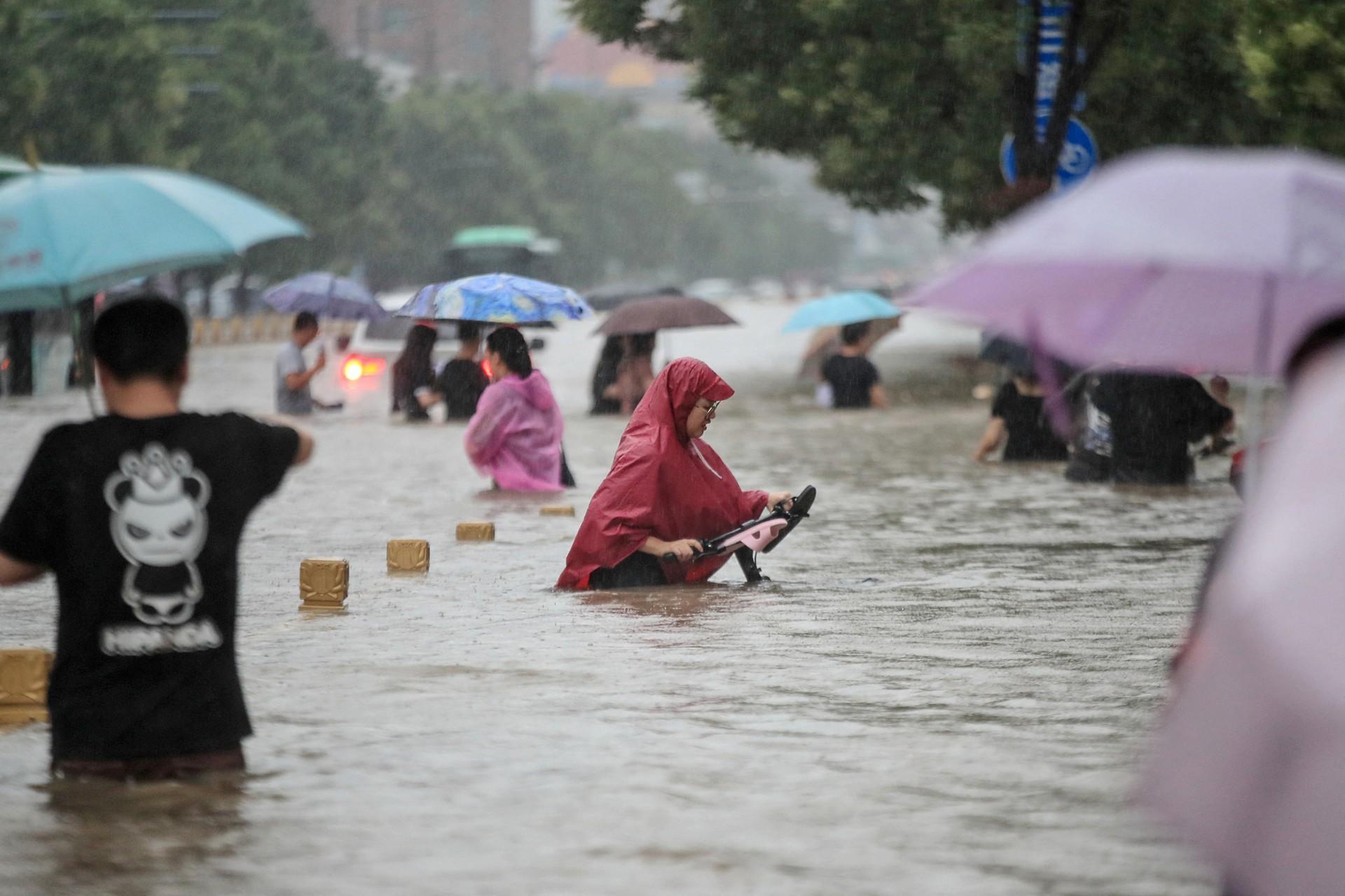 Esta foto tirada em 20 de julho de 2021 mostra pessoas atravessando as águas da enchente ao longo de uma rua após fortes chuvas em Zhengzhou, na província chinesa de Henan. (Foto por STR / AFP) / China OUT  (Foto: STR / AFP/ China OUT )