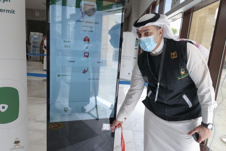 Um membro da equipe saudita digitaliza um cartão de hajj de peregrino, permitindo o acesso sem contato a locais religiosos, acomodação e transporte, em um centro de recepção em Meca em 18 de julho de 2021 (Foto: FAYEZ NURELDINE / AFP)