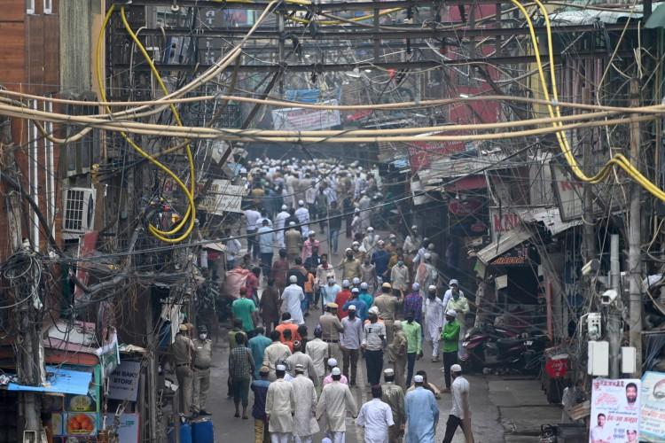 As pessoas se reúnem depois de oferecer orações durante o festival Eid al-Adha, a festa do sacrifício perto de Jama Masjid em Nova Delhi em 21 de julho de 2021 (Foto: Money SHARMA / AFP)