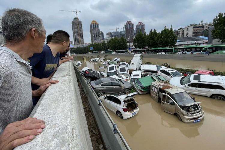 As pessoas olham para os carros parados nas enchentes após fortes chuvas atingirem a cidade de Zhengzhou, na província de Henan, na China, em 21 de julho de 2021 (Foto: STR / AFP)