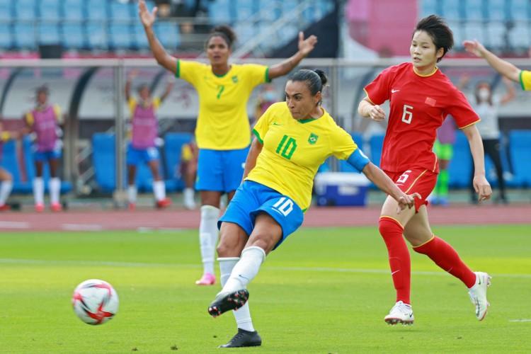 Marta chuta para marcar o primeiro gol na goleada contra a China, na estreia nas Olimpíadas de Tóquio (Foto: Kohei CHIBAGARA / AFP)