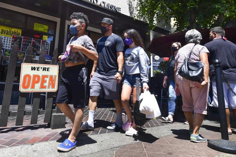 Pessoas passam por restaurantes abertos para negócios em Los Angeles em junho de 2021 (Foto: Frederic J. BROWN / AFP)
