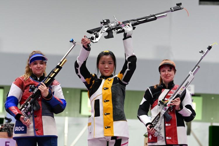 A chinesa Yang Qian comemora no pódio entre a russa Anastasiia Galashina e a suíça Nina Christen após vencer a final da carabina de pressão feminino 10m durante os Jogos Olímpicos de Tóquio 2020 no campo de tiro Asaka, no distrito de Nerima, em Tóquio (Foto: Tauseef Mustafa / AFP))