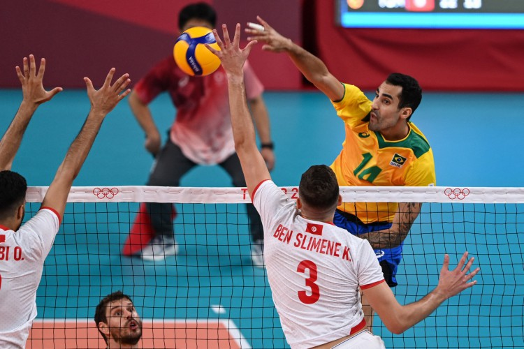 Douglas Correia de Souza (à direita) do Brasil lança a bola na partida masculina de vôlei do Grupo B entre Brasil e Tunísia durante as Olimpíadas de Tóquio 2020 na Ariake Arena em Tóquio em 24 de julho de 2021. (Foto: YURI CORTEZ / AFP) (Foto: YURI CORTEZ / AFP)