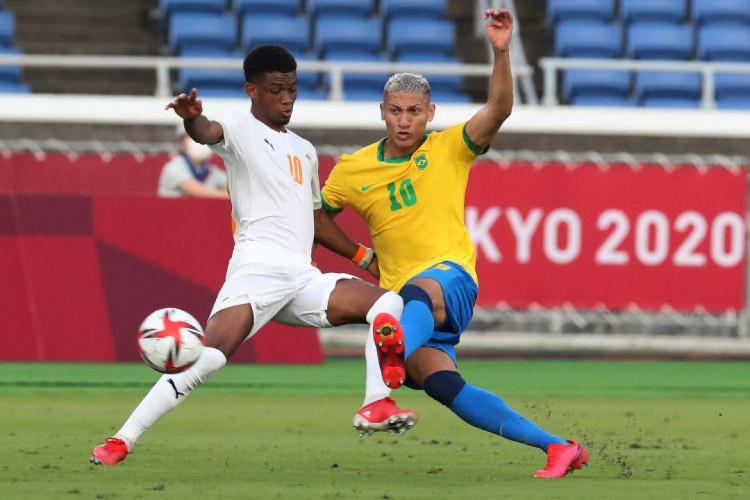 Richarlison disputa bola com Amad Diallo, da Costa do Marfim (Foto: Yoshikazu TSUNO / AFP)