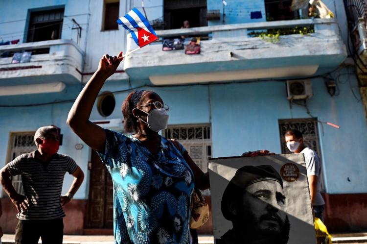 Uma senhora idosa agita uma bandeira cubana segurando um pôster do falecido líder cubano Fidel Castro em Havana, em 26 de julho de 2021. - O governo cubano comemorará em 26 de julho o 68º aniversário do ataque guerrilheiro ao quartel Moncada, amplamente considerado o início da Revolução Cubana. (Foto de YAMIL LAGE / AFP)