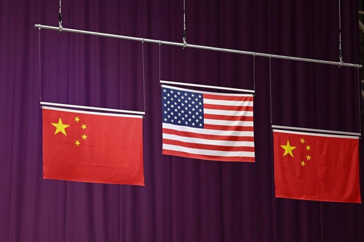 As bandeiras dos Estados Unidos e da China são vistas durante a cerimônia de medalha do medalhista de prata Sheng Lihao da China, do medalhista de ouro dos EUA William Shaner e do medalhista de bronze da China Yang Haoran na final do rifle de ar comprimido masculino 10m durante os Jogos Olímpicos de Tóquio  (Foto: Tauseef MUSTAFA / AFP)