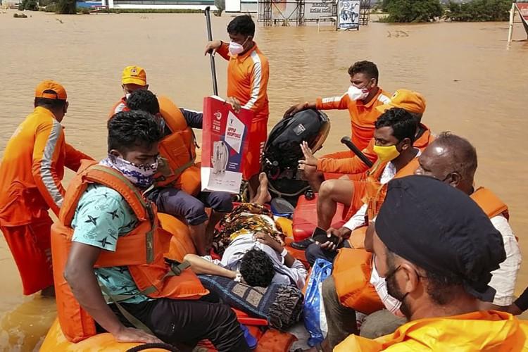 Força Nacional de Resposta a Desastres (NDRF) resgatando pessoas de áreas inundadas pelas águas da enchente na vila de Shiroli no distrito de Kolhapur de Maharashtra, na Índia (Foto: NDRF / AFP)