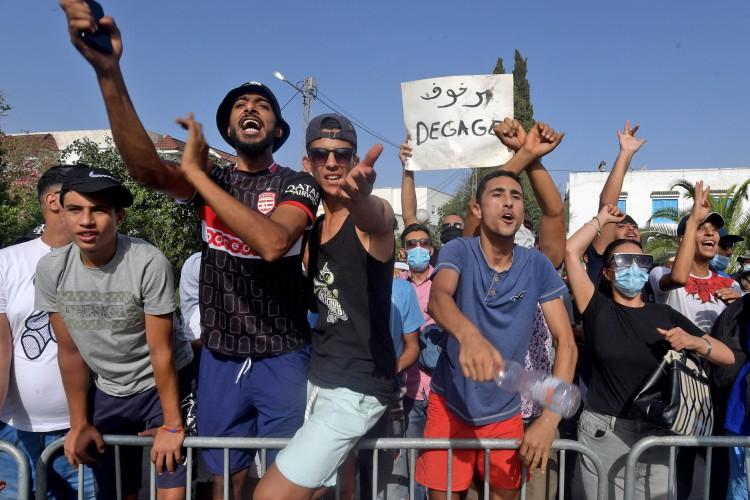 Apoiadores do presidente da Tunísia, Kais Saied, entoam slogans denunciando o principal partido islâmico Ennahda (Ennahdha) diante do Parlamento (Foto: FETHI BELAID / AFP)