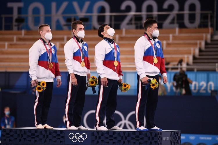 Os atletas comemoram no pódio após vencer a final da equipe masculina de ginástica artística durante os Jogos Olímpicos de Tóquio 2020 no Centro de Ginástica Ariake   (Foto:  Martin BUREAU / AFP)