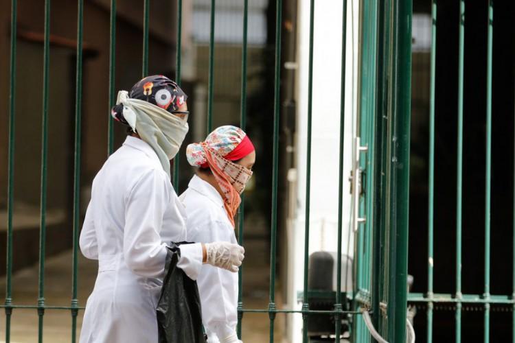 Nas ruas da cidade, pesssoas se protegem utilizando mascaras descartaveis, luvas, proteção no cabelo,para proteger contra o novo coronavírus, no primeiro dia de comércio fechado por determinação da prefeitura do Rio (Foto: Tania Regô/Agência Brasil)