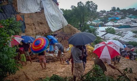 Refugiados Rohingya trabalham em meio aos destroços de casas no campo de Balukhali em 27 de julho de 2021, que foram danificadas depois que as chuvas de monções