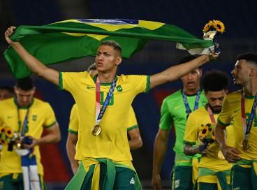 O brasileiro Richarlison comemora após receber sua medalha durante a cerimônia de medalhas da competição de futebol masculino dos Jogos Olímpicos de Tóquio 2020, no Estádio Internacional de Yokohama, em Yokohama, Japão, em 7 de agosto de 2021. (Foto de Anne-Christine POUJOULAT / AFP)