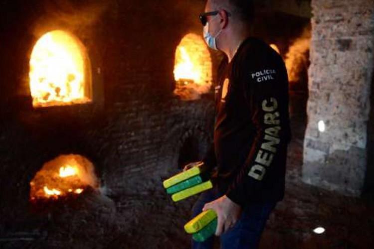 Policial Civil deposita tabletes de cocaína em estufas durante processo de incineração realizado em junho deste ano, em Aquiraz
