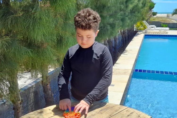 Miguel Pitombeira, 9 anos, gosta do barulho que as bolinhas do brinquedo fazem. A mãe estimula o uso consciente desse e de outros brinquedos