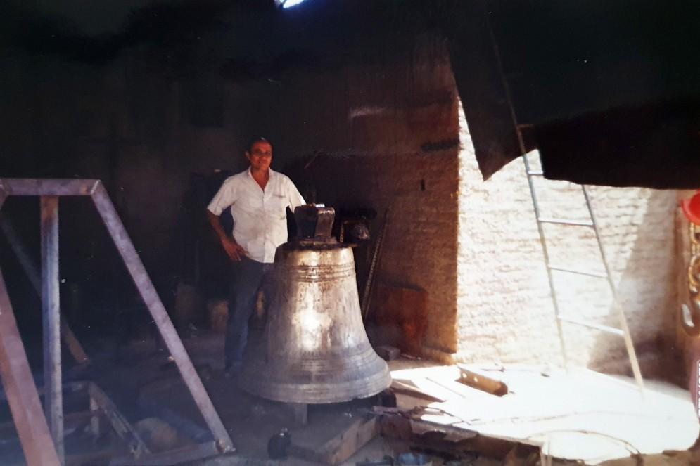 Geraldo Ramos Freire posa pra foto ao lado de sino de igreja produzido na sua oficina, em Juazeiro do Norte(Foto: Arquivo pessoal)