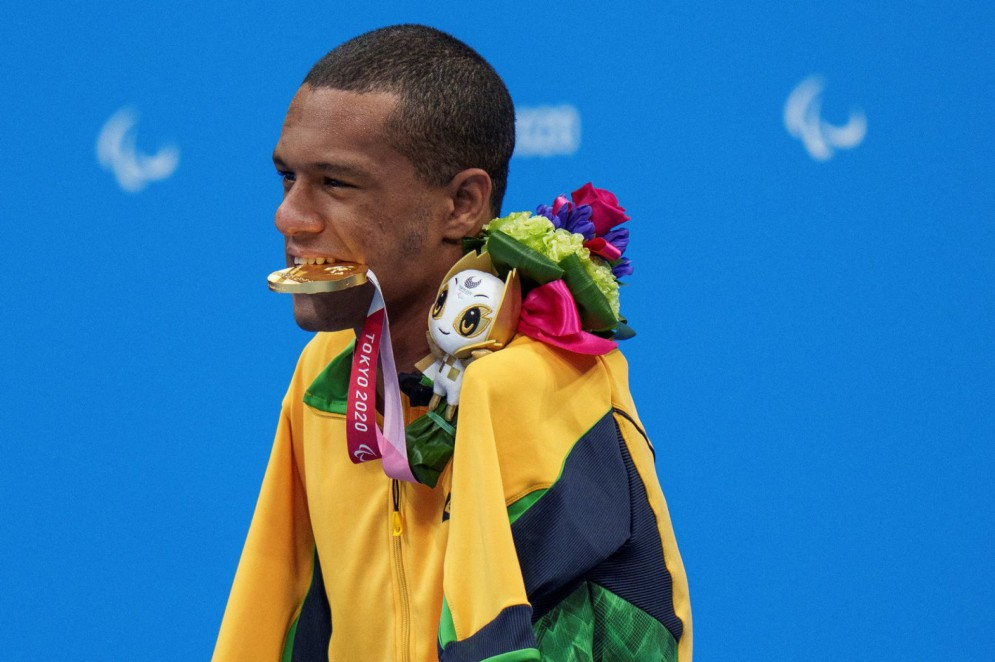 This handout photo released by the Olympic Information Services (OIS) of the International Olympic Committee (IOC) and taken on September 2, 2021 shows gold medallist Brazil's Gabriel Geraldo Dos Santos Araujo celebrating during the victory ceremony for the men's 50m backstroke S2 swimming event at the Tokyo Aquatics Centre during the Tokyo 2020 Paralympic Games in Tokyo. (Photo by Thomas LOVELOCK / OIS/IOC / AFP) / ---- EDITORS NOTE ---- RESTRICTED TO EDITORIAL USE - MANDATORY CREDIT