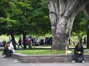 Pessoas sentam-se depois de serem realocadas perto da Porte de la Villette, norte de Paris, em 24 de setembro de 2021, após uma operação policial para expulsar usuários de crack no distrito de jardins Eole