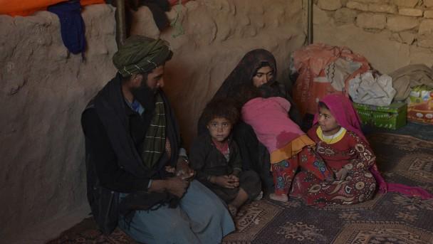Crianças que foram recentemente vendidas às famílias de seus futuros maridos, sentadas com seus pais dentro de uma tenda no campo de Pessoas Deslocadas Internamente (IDP) de Shamal Darya em Qala-i-Naw, província de Badghis
