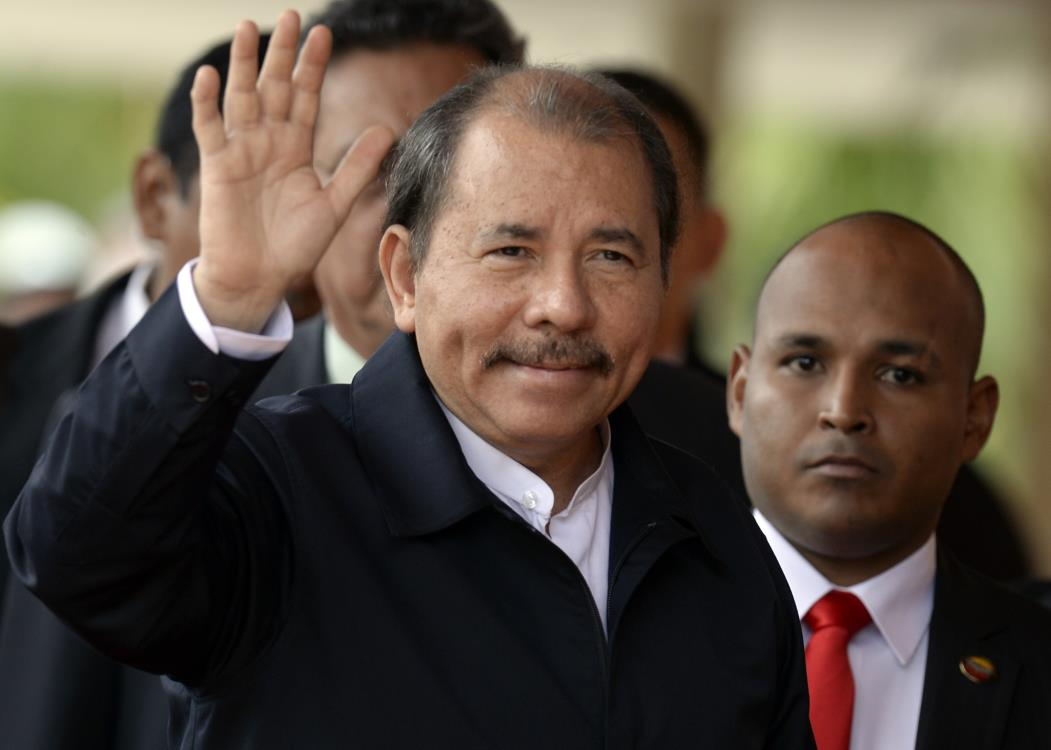 Nicaraguan President Daniel Ortega waves as he arrives for the opening of the Petrocaribe Summit, in Caracas, on May 5, 2013. Pertocaribe is an alliance Venezuela has with several Caribbean states under which it supplies oil to them at cut-rate prices.   AFP  PHOTO / JUAN BARRETO
