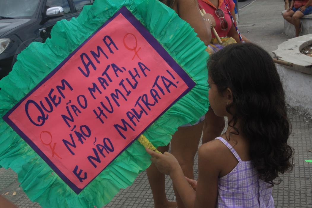Criança com cartaz de protesto contra a violência contra a mulher, no cruzamento das avenidas Godofredo Maciel com Perimental, no Mondubim.