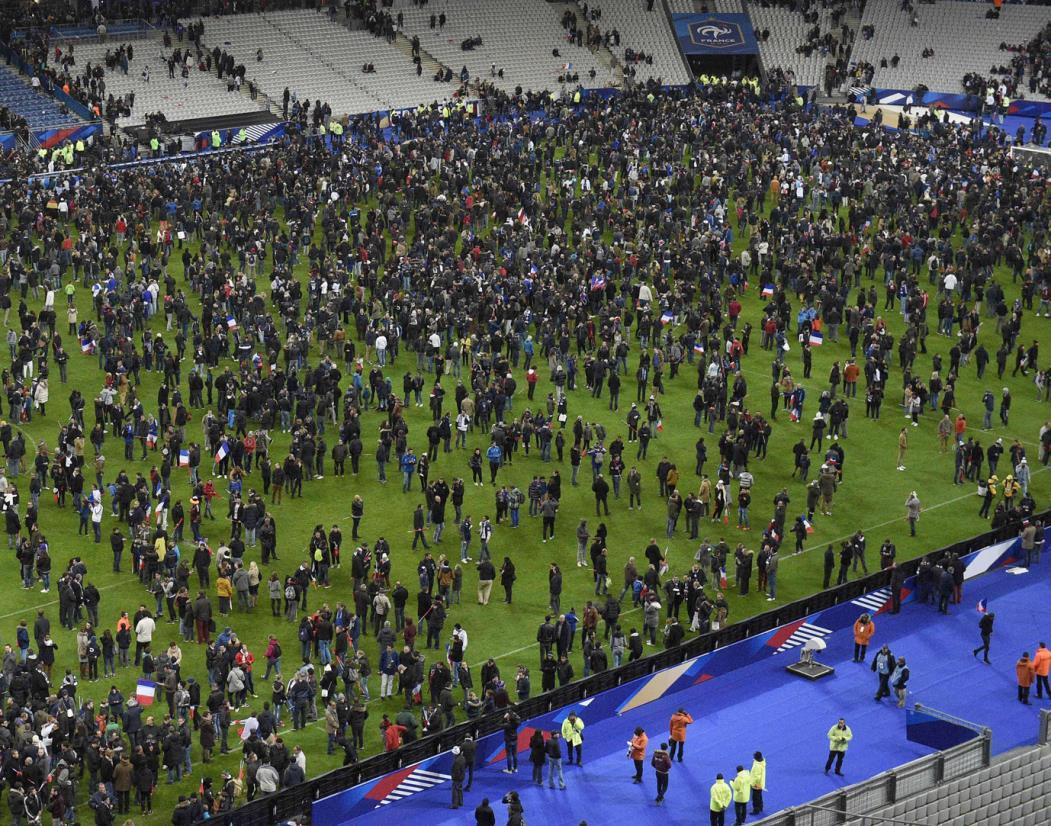 Torcedores se reúnem no campo do Stade de France após o amistoso entre a França e a Alemanha em Saint-Denis, ao norte de Paris, em 13 de novembro de 2015, após uma série de ataques com armas de fogo na capital francesa, bem como explosões fora do estádio nacional onde a seleção da casa recebia a Alemanha. FOTO AFP / FRANCK FIFE(Foto: FRANCK FIFE)