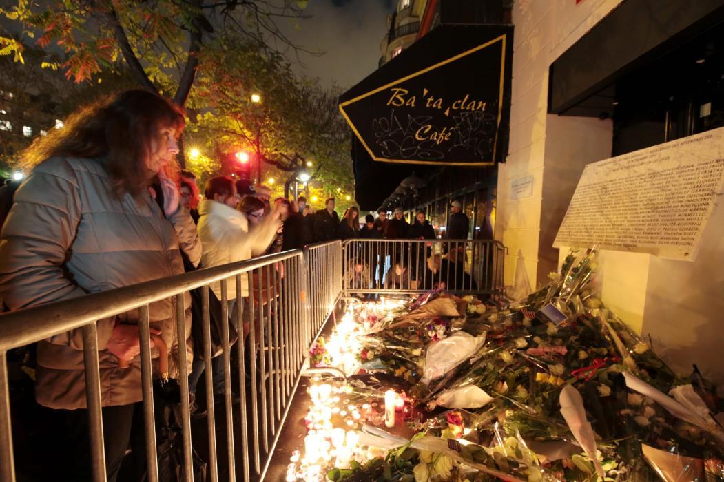 Uma mulher está em frente a uma placa comemorativa e flores em frente ao Bataclan em Paris em 13 de novembro de 2016, quando a França marcou o primeiro aniversário dos ataques em Paris. 130 pessoas foram mortas em 13 de novembro de 2015 por homens armados e homens-bomba do grupo do Estado Islâmico (EI) em uma série de ataques coordenados em Paris e arredores. / AFP PHOTO / JOEL SAGET(Foto: JOEL SAGET)