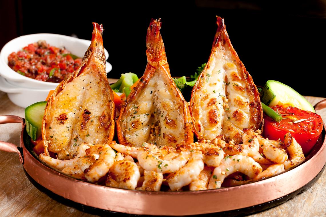 O prato: Três caudas de lagosta e camarões grelhados com azeite e alho. Acompanham legumes salteados, arroz com brócolis e azeite aromatizado.
