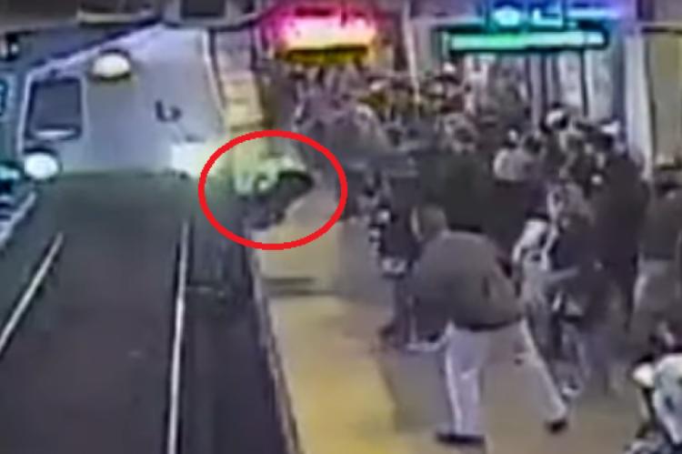 o funcionário segura o homem pelos ombros e o puxa antes do trem atingi-lo