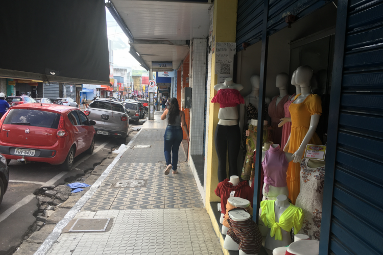 Loja de confecções funcionando à meia porta em Juazeiro do Norte nesta sexta-feira, 9 de abril (Foto: Luciano Cesário/O POVO)