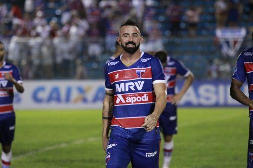 Atacante Leandro Cearense caminha no grsmado sorrindo, em dia de jogo