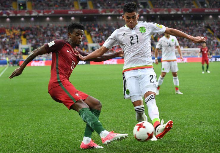 Um jogador de Portugal e um do México disputam a bola por baixo, com os pés (Foto: )