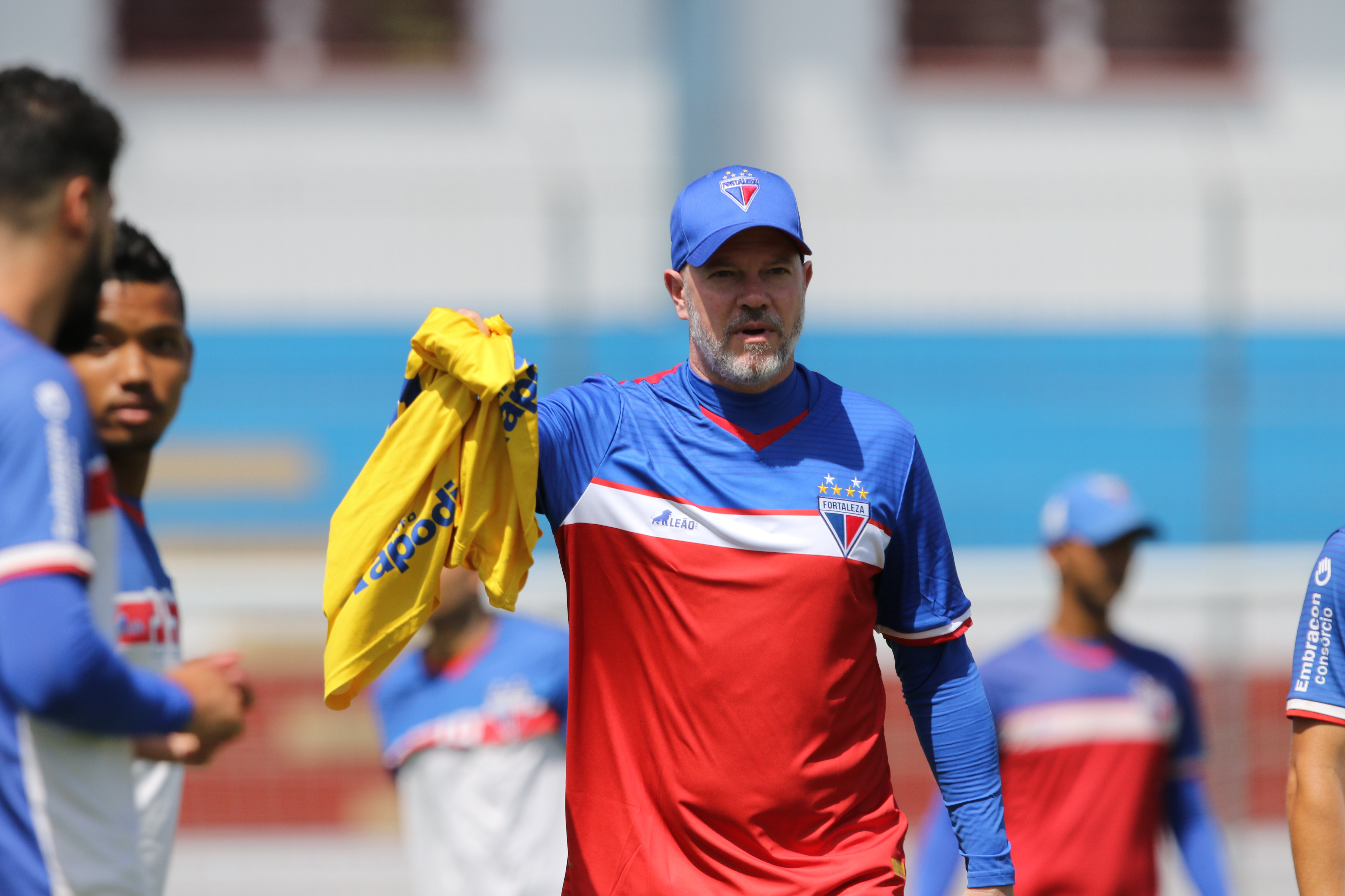 Técnico Zago, em treino do Fortaleza, entregando um colete a um jogador (que não aparece na foto)