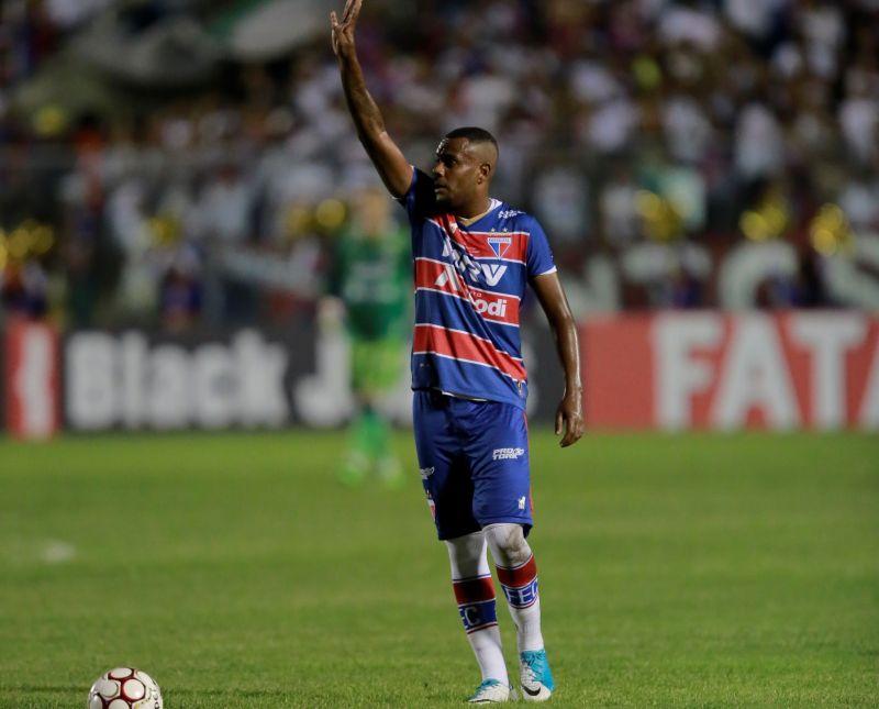 Adenilson, com o braço levantado, sinalizando e uma bola próxima dele