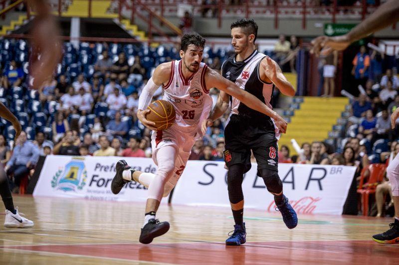 Jogador do Basquete Cearense correndo com a bola e sendo marcado de perto por um jogador do Vasco