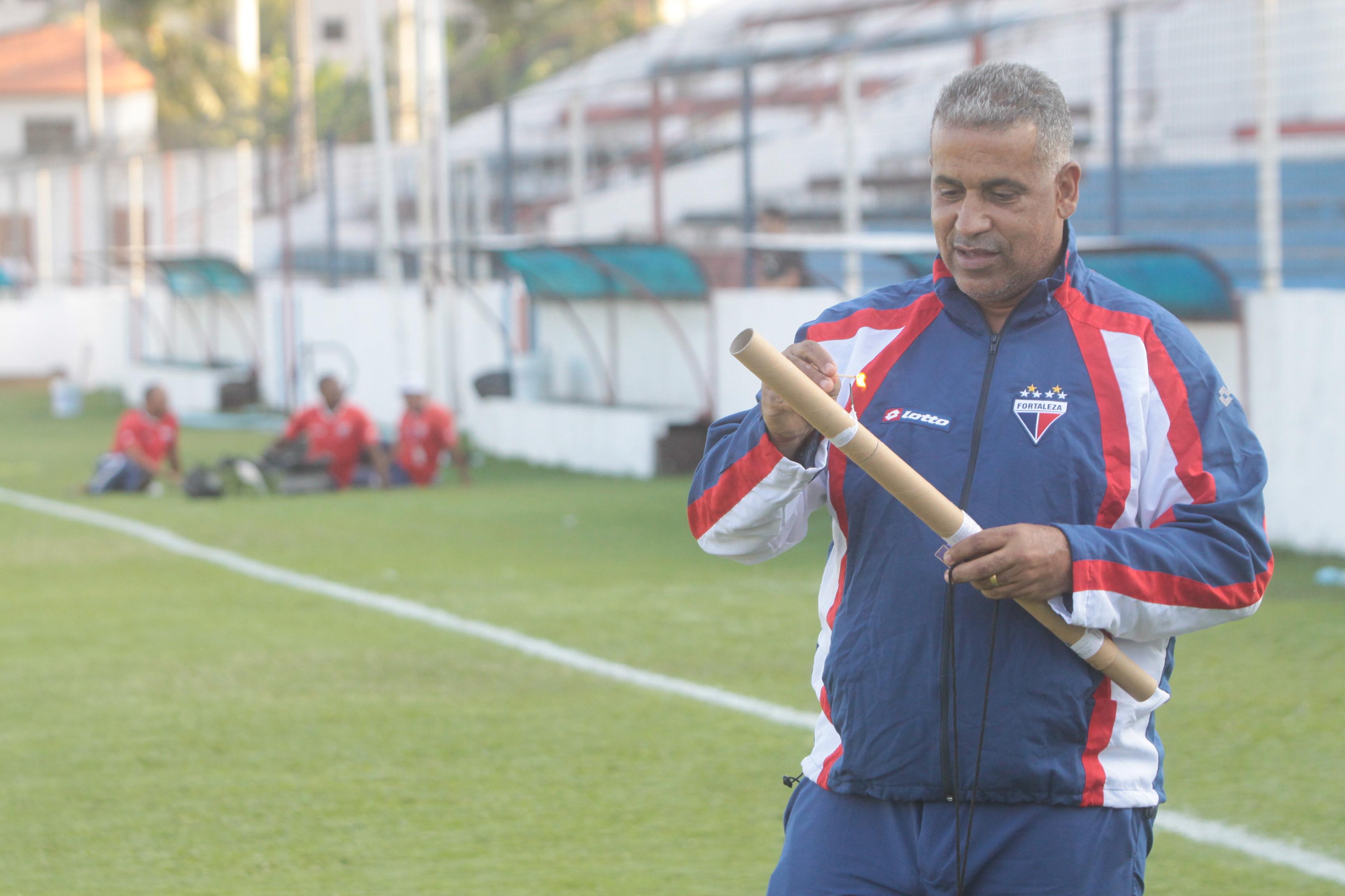 Técnico Ademir Fonseca com agasalho do Fortaleza e ascendendo um rojão