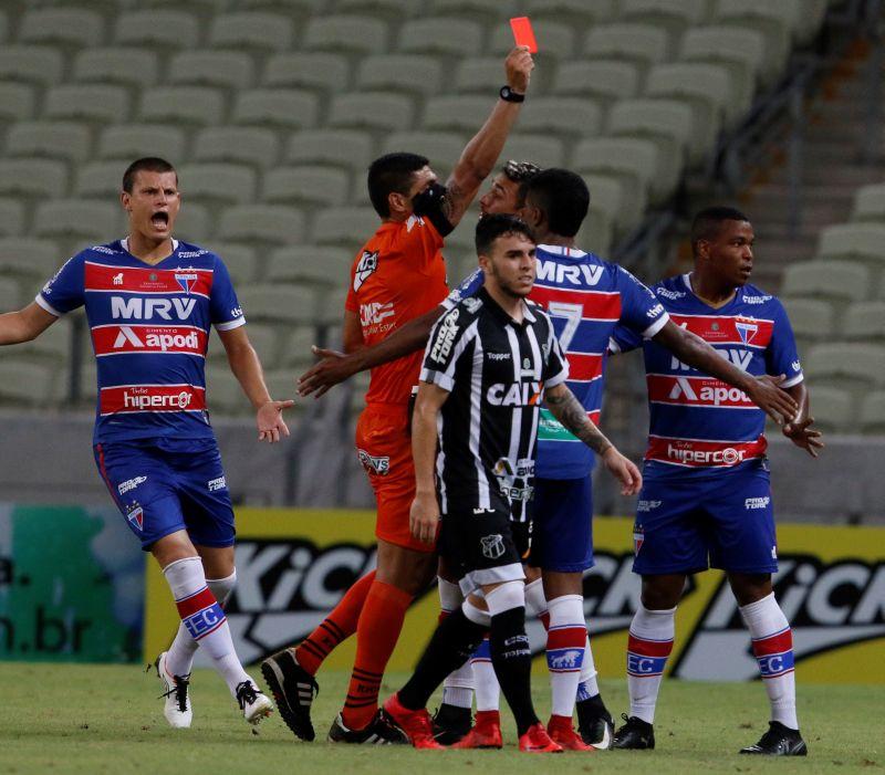 Árbitro dando cartão vermelho, cercado de atletas do Fortaleza e do Ceará