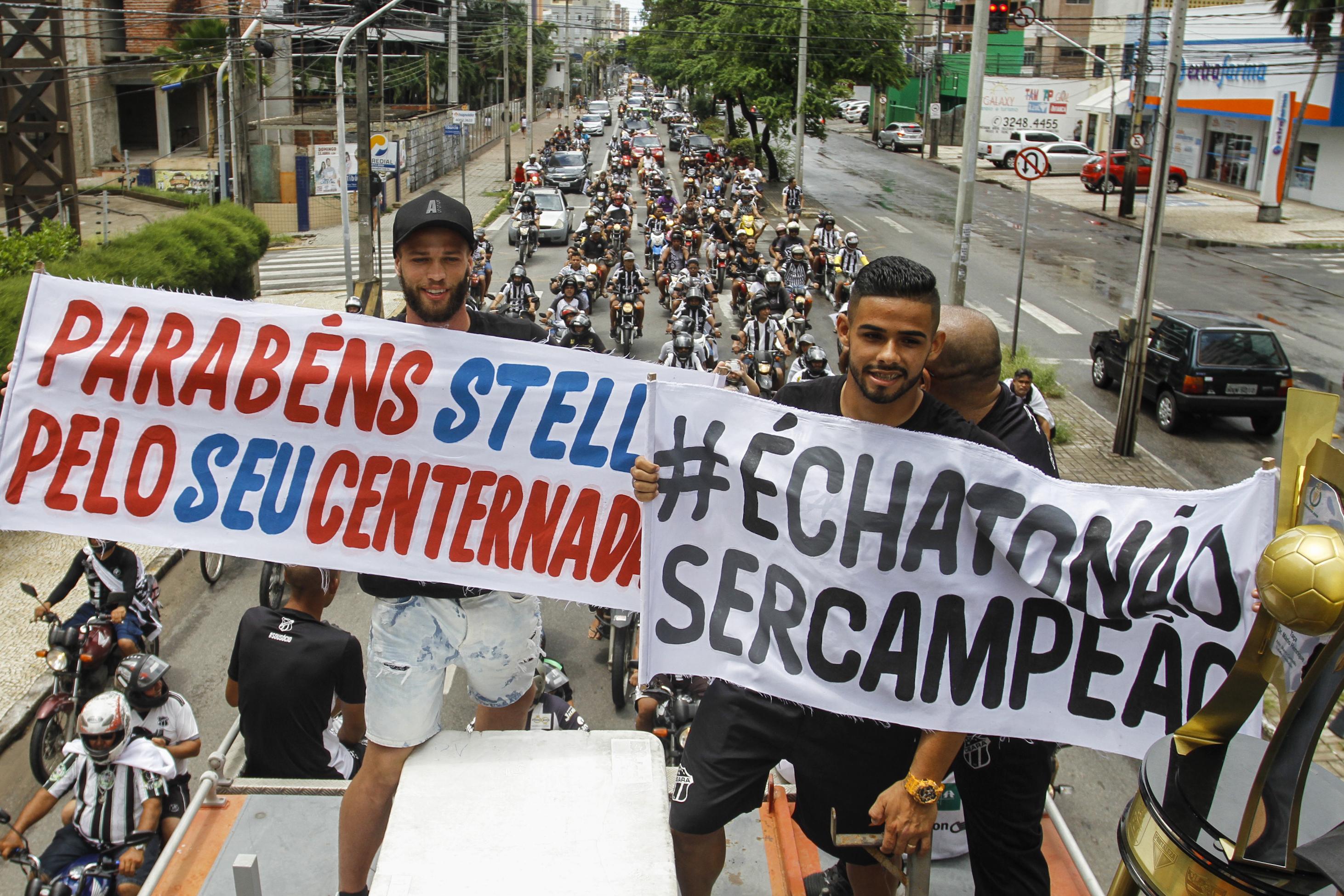 Jogadores com faixa de comemoração do título do Ceará e outra de provocação ao Fortaleza pelo