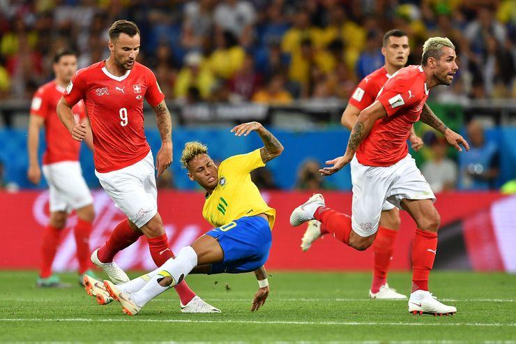 Neymar, com meias rasgadas e caído entre marcadores suíços