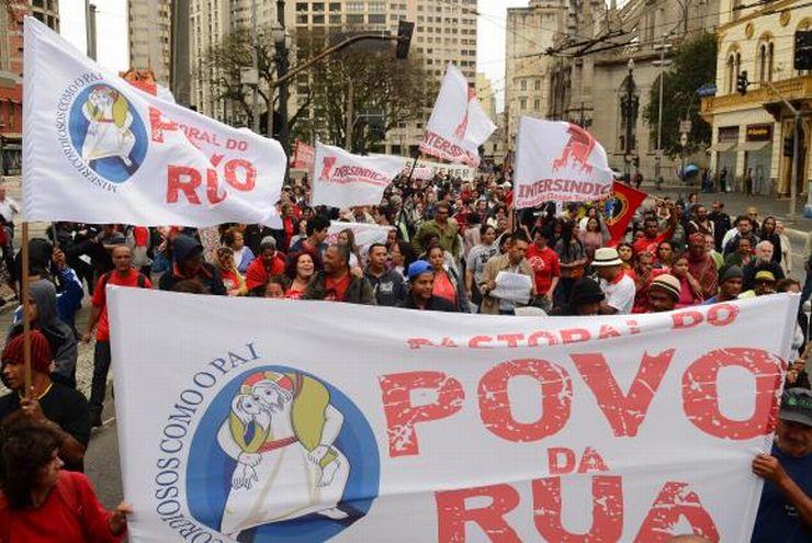 Multidão carrega bandeira da Pastoral da Povo na Rua, na praça da Sé, em São Paulo