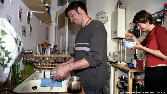Homem lava louça enquanto mulher segura um prato