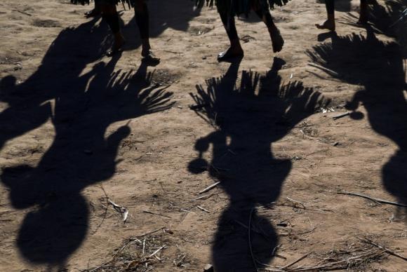 índios dançam em ritual e suas sombras são registradas no chão da tribo