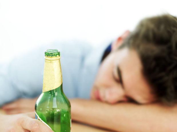 Homem deitado na mesa bêbado com uma garrafa de cerveja na mão