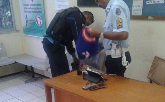 Dois policiais seguram camisas do Capitão América, em alusão do candidato Capitão Wagner. A cena se passa numa delegacia