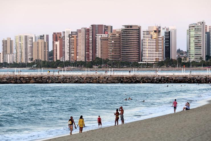 Foto da orla de Fortaleza em que os turistas passeiam pelo aterro da Praia de Iracema