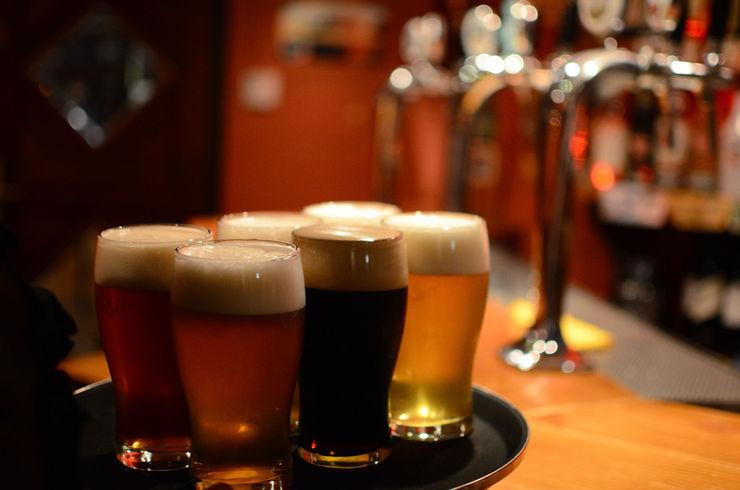 Uma bandeja em cima de uma balcão com quatro cervejas