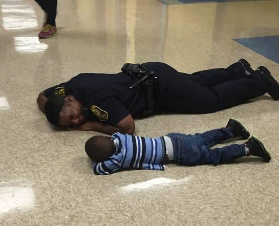 Policial deitada no chão consolando um menino de 4 anosl