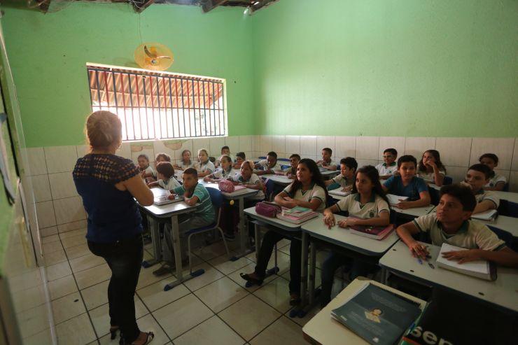 Numa sala de aula, uma professora está de costas e um grupo de 22 alunos olha em direção a ela