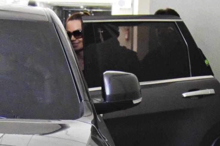 A cantora Solange Almeida entra em um carro com um leve sorriso no rosto após deixar a Superintendência da Polícia Federal, em Fortaleza